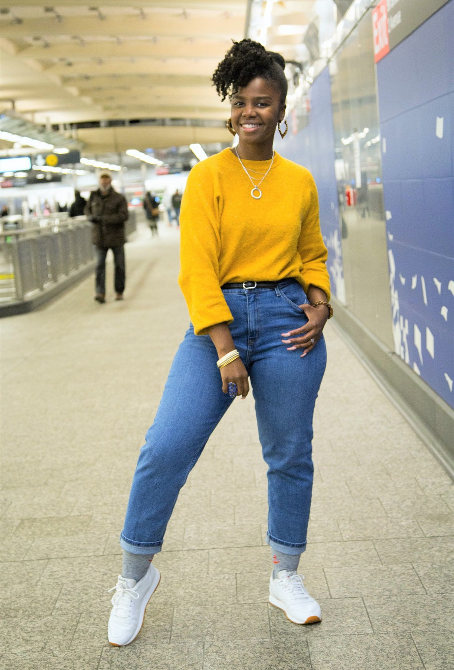 black woman wearing a yellow cozy fall sweater, posed in a NYC train station with one hand in jeans pocket.